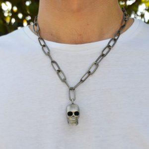 Colar corrente larga de metal com caveira pendente. Este colar é curto e possui fecho mesquetão com terminal de corrente ajustável.